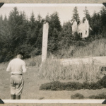Man in front of totem pole and Russian Church