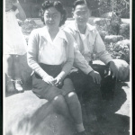 Photograph of Dr. and Mrs. Jiro Muramoto with daughter posing in front of the Manzanar hospital