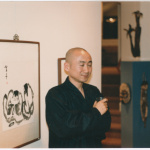A man in an art show with sumi-e paintings