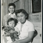 Photograph of two women an a young child posing in front of the infirmary at Cow Creek Camp in Death Valley