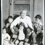 Photograph of Grandpa Tayama surrounded by four children in front of a door in Cow Creek Camp in Death Valley