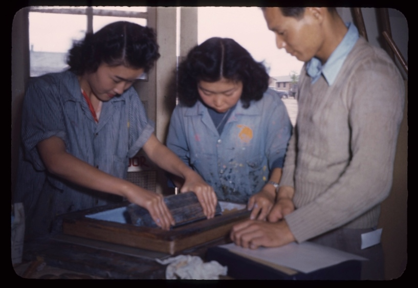 Three Nikkei silk screen workers focused on the task at hand.